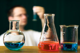 Chemistry research concept with flasks and a blurred scientist poster