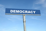 Metal signpost spelling Democracy over blue sky poster