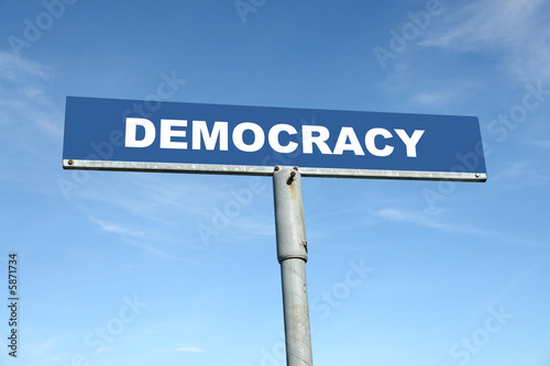 poster of Metal signpost spelling Democracy over blue sky
