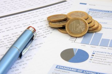 Financial reports, euro coins and a blue pen