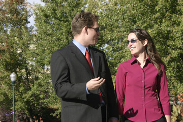 businessman and businesswoman talk while walking outside