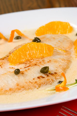 Closeup of grilled skate (ray) with ogange and caper sauce.