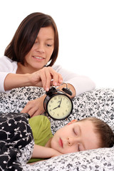 mother trying to wake up 6 years old boy /focus on clock/