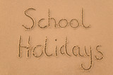 School Holidays handwritten in sand. poster
