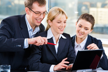 Three business people looking into the screen of a laptop