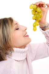 Girl with a cluster of green grapes, isolated on white..