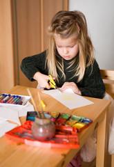 Kind bastelt und malt