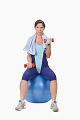 Woman with bar-bells sitting on a gym ball.