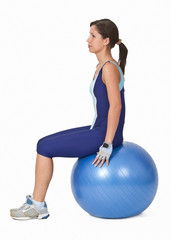 Young active woman sitting on a blue fitness ball