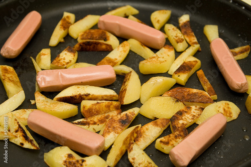 potato and sausages frying on the pan