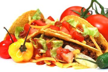 Closeup of tacos with tomatoes, habanero and serano peppers.