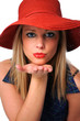 Beautiful young girl with red hat blowing a kiss