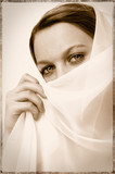Beautiful young woman with veil on her face revealing eyes poster