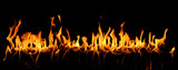 Tongues of fire in a panoramic view over a black background.