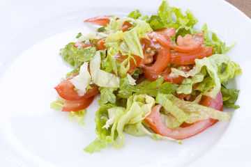 Salad from tomatoes and fresh lettuce with green