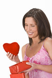 Woman taking out a plush heart from a gift box. poster