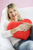 young woman in her 20s, holding a heart-shaped cushion poster