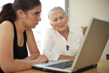 Grandmother and granddaughter with laptop. poster