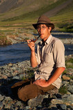 man is smoking tobacco-pipe near the stream poster