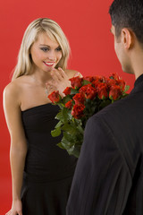 Young man in suit is giving flowers to  woman