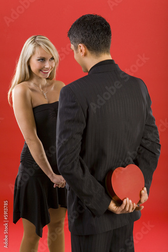 Young man in suit is hiding gift before woman