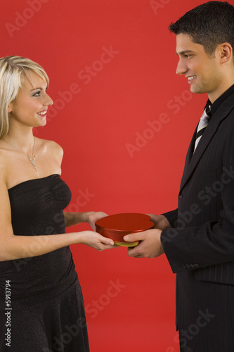 Handsome man in suit is giving beautiful woman  chocolates