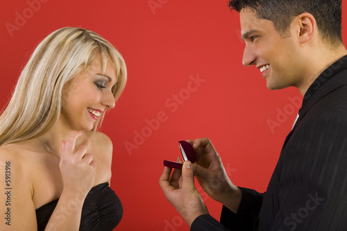 Young enamoured couple. Man is giving ring to the woman.