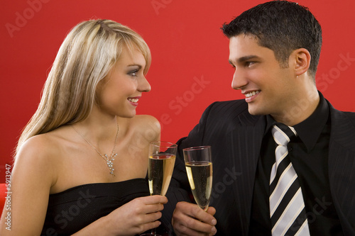 Young couple sitting on couch and rising toast.