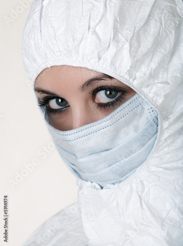 Woman dressed in white operating coat  with mask.
