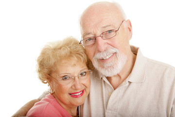 Senior couple wearing glasses.  White background.