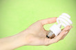 female hand holding a CFL bulb on green background
