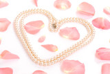 Heart shaped from string of pearls among pink rose petals poster