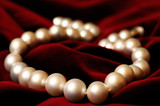 Necklace made out of real pearls on deep red velvet background poster