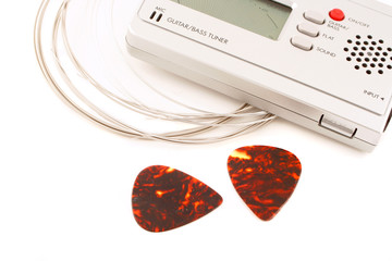 a guitar and bass portable string tuner, strings and picks