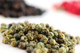 Heaps of green, black and red peppercorns on white background poster