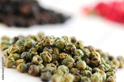 Heaps of green, black and red peppercorns on white background