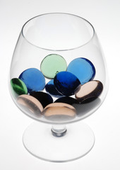 multicolored stones in wineglass against white background