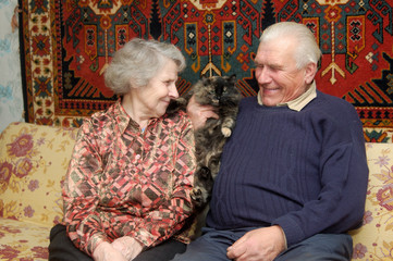 Seventy year old cople smiling in home on sofa