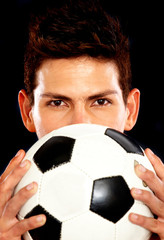 male football player holding a ball over black
