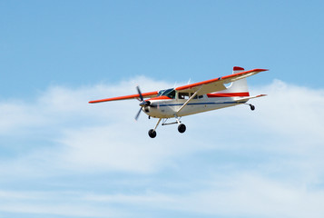 Cessna 180 with flaps down on final approach