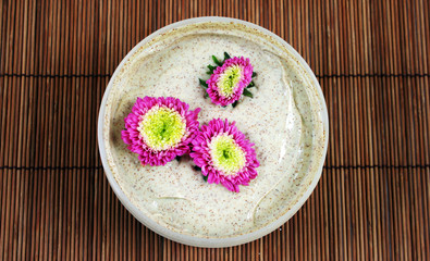 Spa and beauty products - body scrub with pink flowers.