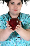 Beautiful young nurse or dental assistant offering an apple. poster