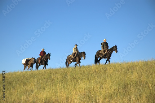Three cowboys moving into the backcountry with supplies