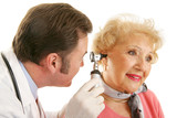 Doctor using otoscope to look inside  woman's ears.