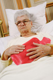 Sick senior woman with hot-bottle water poster