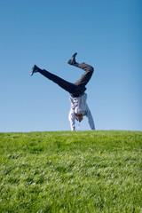 Happy businessman doing summersault on grass