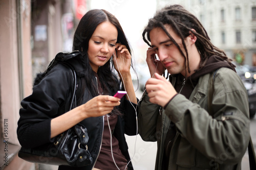 Young couple listening to a portable music player on a street