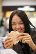 Beautiful girl eating hamburger and laughing. Shallow DOF.
