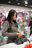 Fototapety Beautiful girl shopping in a store. Shallow DOF.