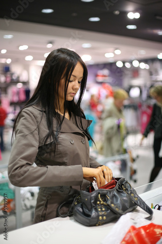 Beautiful girl shopping in a store. Shallow DOF.